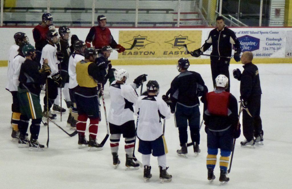 Teaching on ice hockey strategies to the athletes at hockey camp