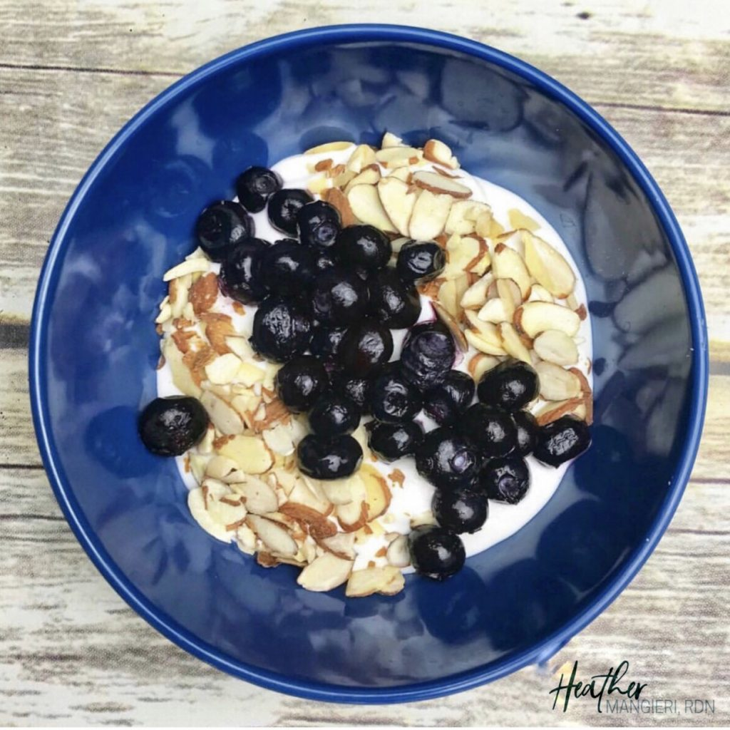 Plain Greek yogurt Topped with Fresh Blueberries and Slivered Almonds