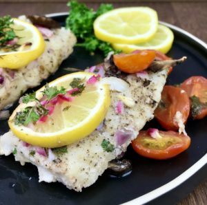 This lemon baked cod recipe is super to prepare and makes a great family meal. This recipe uses with ~14 ounces of raw cod. You can buy a fresh cod fillet, or you can buy frozen, pre-portioned fillets. If you use frozen, you'll want to defrost the fish first. While the oven is pre-heating, get all of the ingredients measured and prepared. The recipe incorporated quite a few vegetables and herbs that need cut in advance. Slice the cherry tomatoes and mushrooms, then chop the onions, garlic and fresh parsley. You'll also need butter, lemon juice and a fresh lemon. Prepare and measure these ingredients, then set them aside. To start, preheat oven to 400 degrees. Spray a baking dish with cooking spray, then set it aside and prepare the fish. If you are using a fresh cod fillet, slice it into 4 equal fillets, ~3.5 ounces each. Pat it dry, then sprinkle with salt and pepper. Transfer the cod fillets to a baking dish, then top with the sliced mushrooms and cherry tomatoes. Melt the butter in a small bowl, then add the lemon juice, onions, garlic and parsley. Stir those ingredients together well, then pour over the fillets. If you have a fresh lemon, lay a slice top of each fillet and sprinkle with additional parsley. Your fish is ready to bake. Transfer it to the oven and allow it to cook for ~20 minutes or until it is opaque and flakes with a fork. I highly suggest checking it with a food thermometer to be sure it is done. It is fully cooked when the internal temperature reaches ~145 degrees F. This lemon baked cod is great served with rice and a green salad, or your favorite vegetable. I hope you enjoy it.