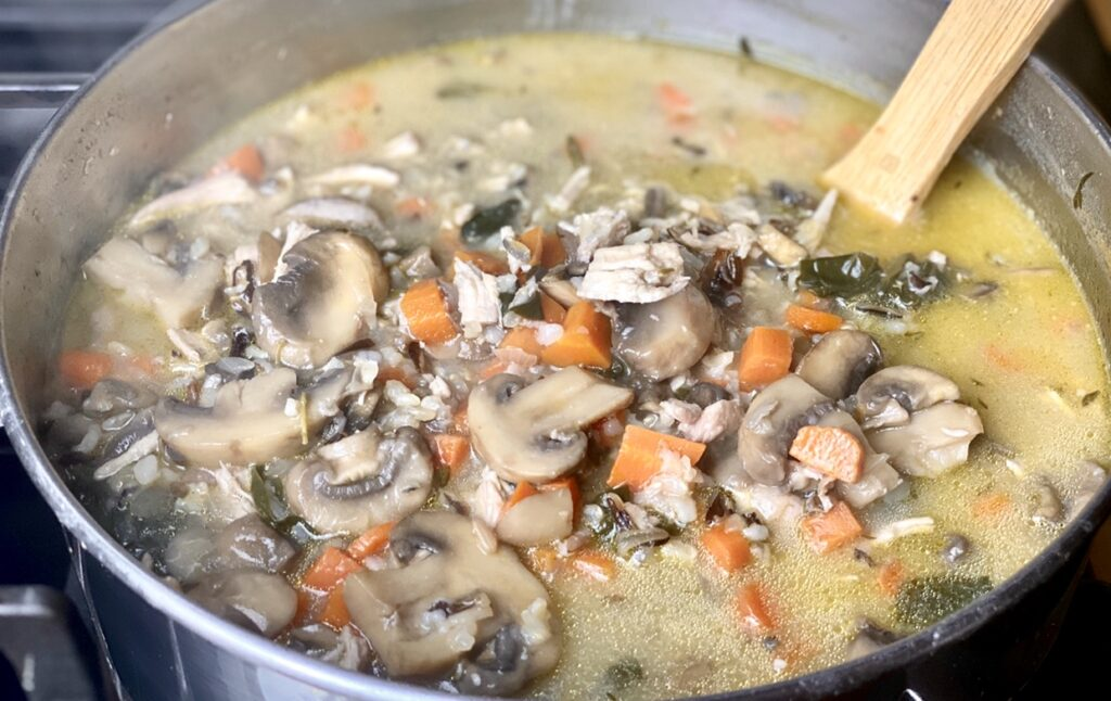 Cream of Chicken and Mushroom Soup with Wild Rice simmering on the stove top